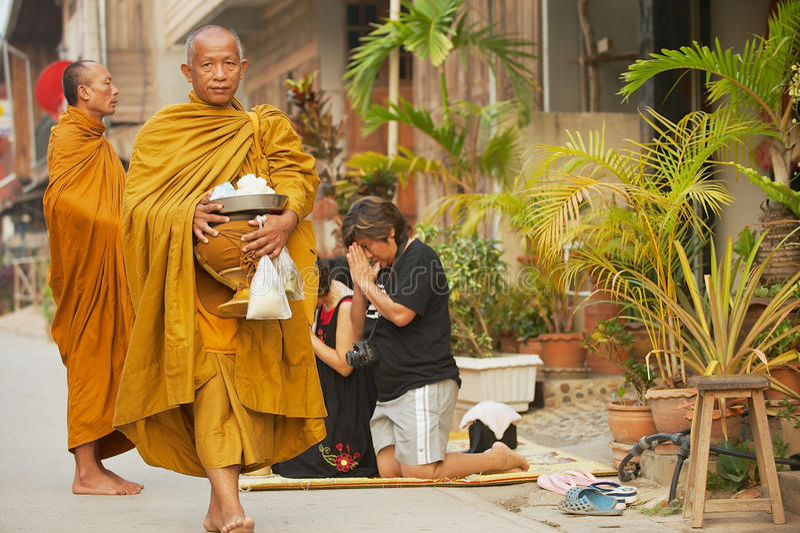 El monje camina por la calle con donaciones de la gente local en la madrugada en Chiang Khan, Tailandia fotografía de archivo libre de regalías