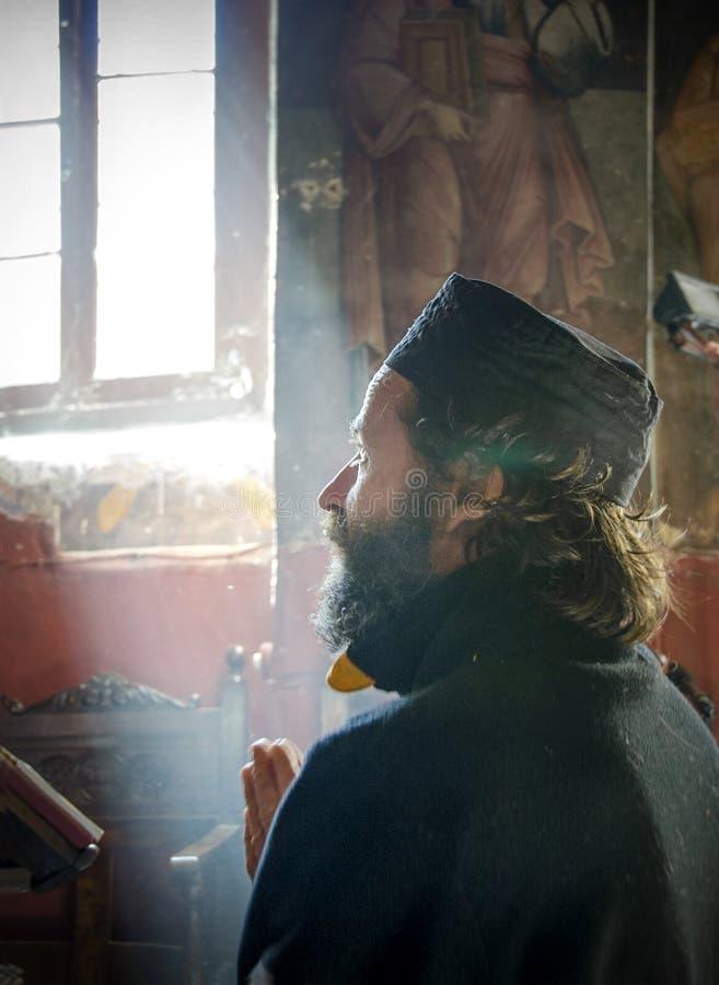 El monje de Christian Orthodox ruega el monasterio interior de San Jorge en Corinto, Grecia fotografía de archivo