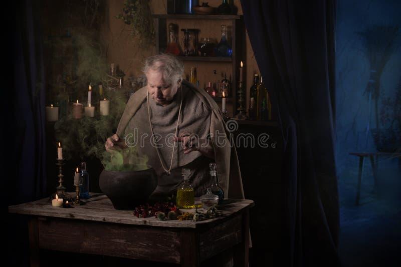 El monje mayor del alquimista elabora cerveza la poción mágica imagen de archivo