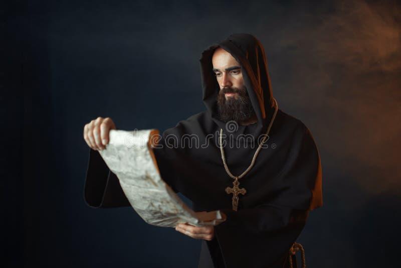 El monje medieval con una cara malvada lee un rezo fotos de archivo