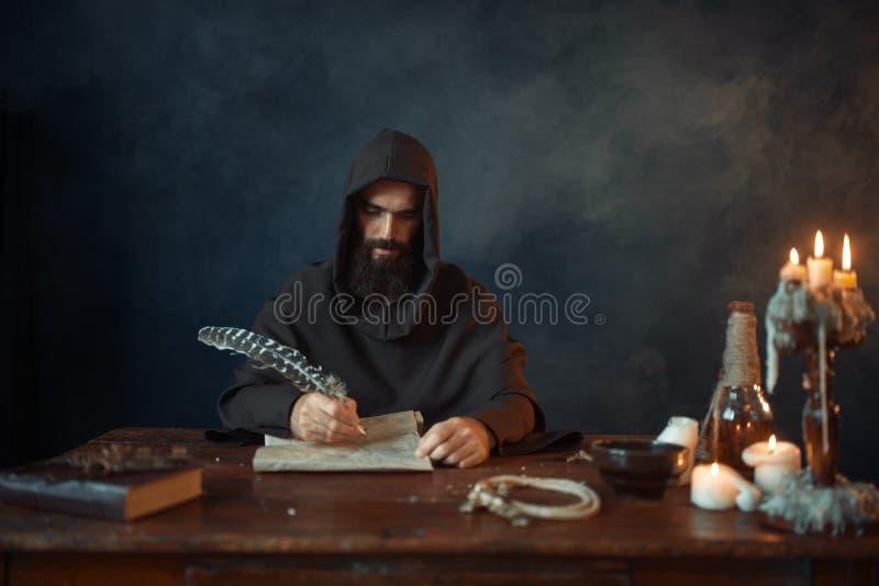El monje medieval en traje escribe con una pluma del ganso imágenes de archivo libres de regalías