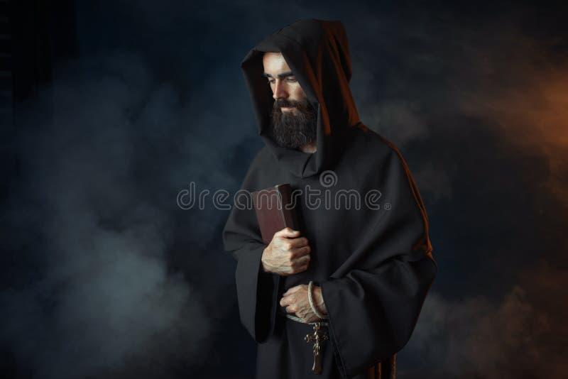 El monje medieval en traje lleva a cabo el spellbook en manos imágenes de archivo libres de regalías