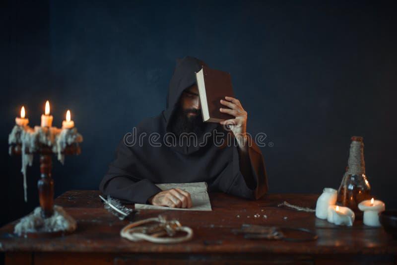 El monje medieval que se sienta en la tabla y lee foto de archivo