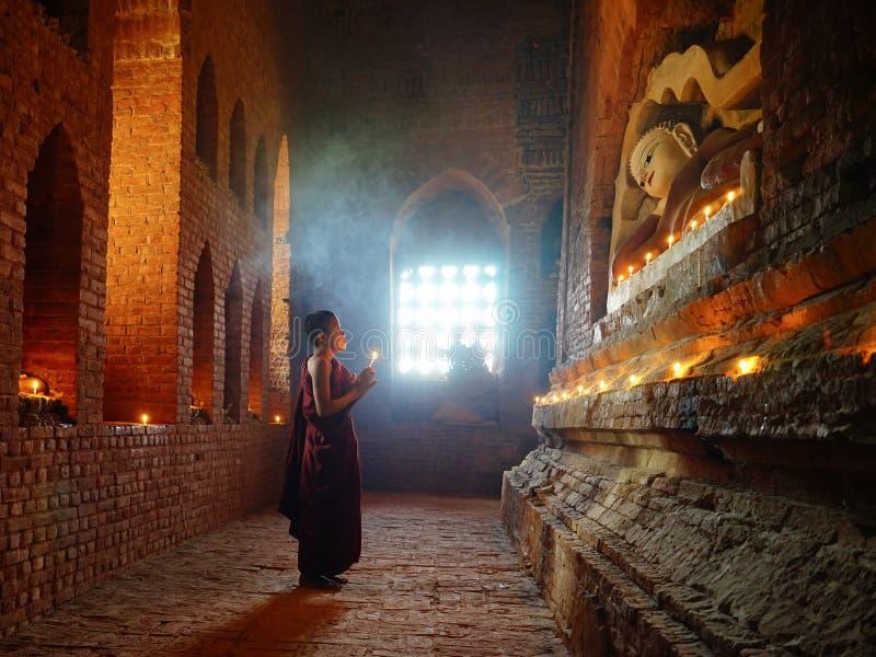 El monje ruega con la vela en Bagan, Myanmar imagenes de archivo