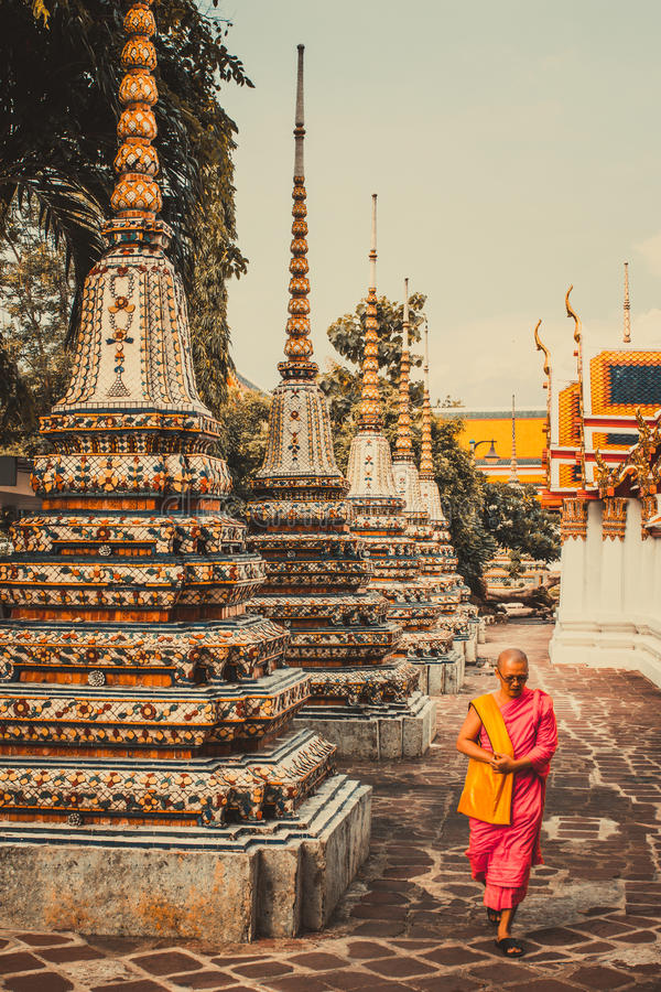El monje tailandés está caminando delante de pagoda antigua vieja en Wat Pho Temple en Bankgok, Tailandia imágenes de archivo libres de regalías