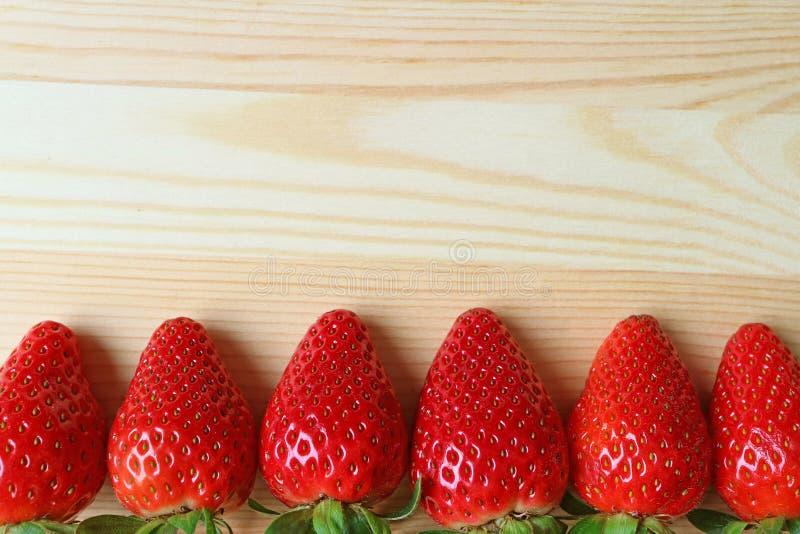 El montón de la fresa madura fresca da fruto Lind para arriba en la tabla de madera con el espacio de la copia imágenes de archivo libres de regalías