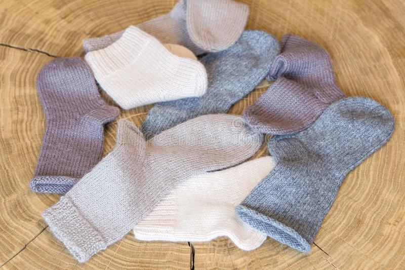 El montón de pequeña diversa cachemira coloreada linda hizo punto calcetines recién nacidos del bebé en un fondo de madera del es fotografía de archivo