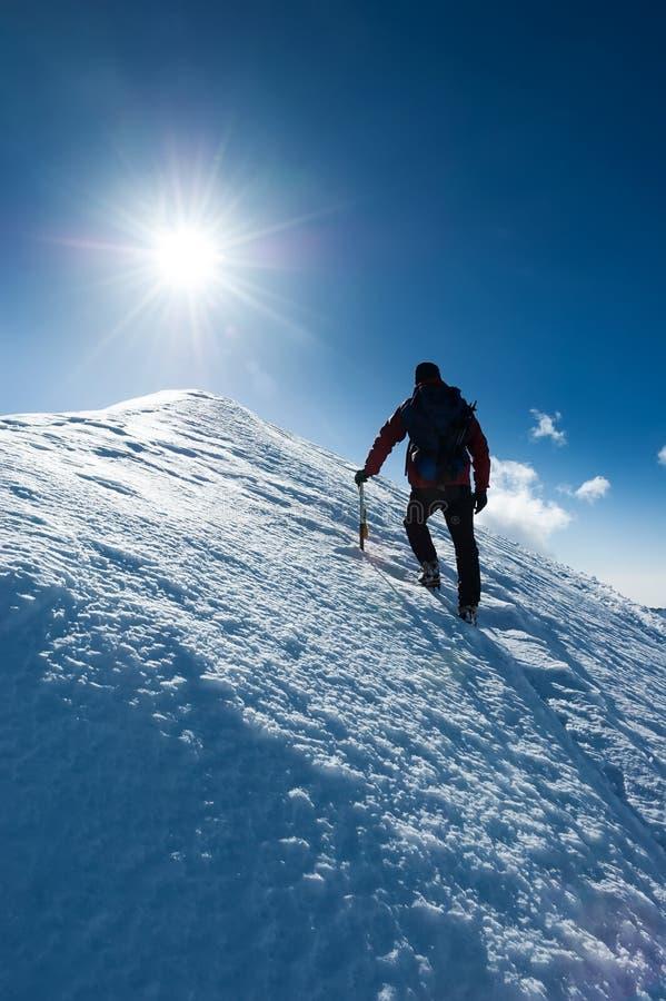 El montañés alcanza la cumbre de un pico nevoso Concepto: valor fotos de archivo