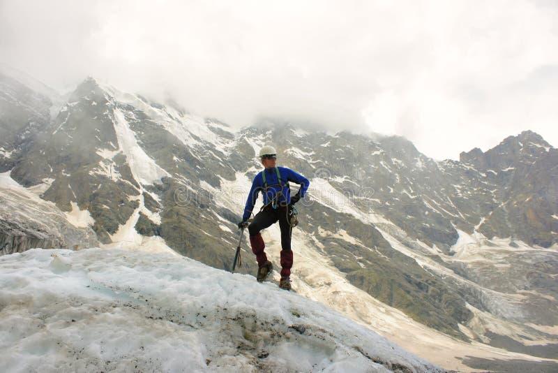 El montañés con el hacha de hielo se coloca encima del glaciar fotografía de archivo