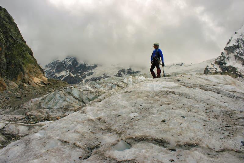 El montañés con el hacha de hielo se coloca encima del glaciar fotografía de archivo libre de regalías