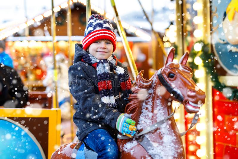 El montar a caballo adorable del muchacho del niño en un feliz va caballo del carrusel de la ronda en el funfair o el mercado de  imagenes de archivo