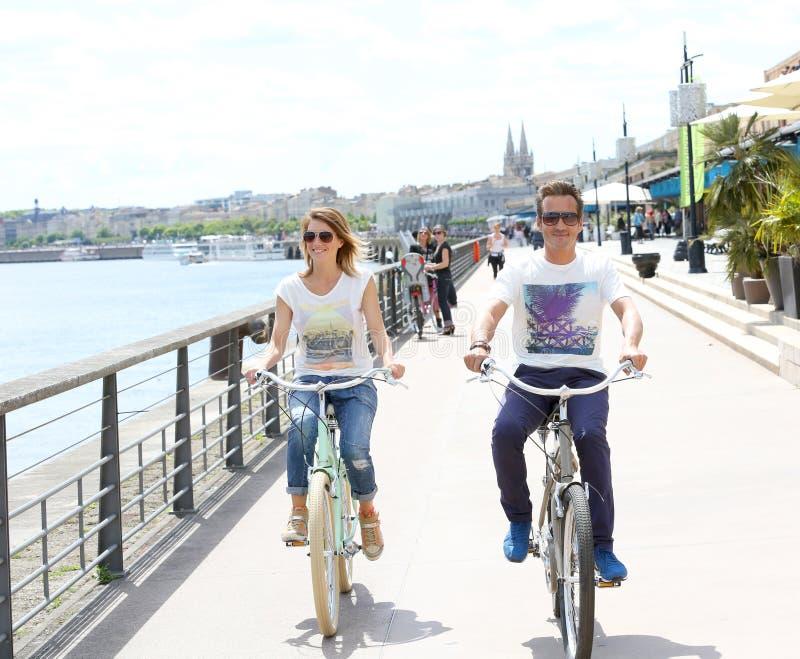 El montar a caballo alegre de los pares bikes en ciudad por el río fotografía de archivo