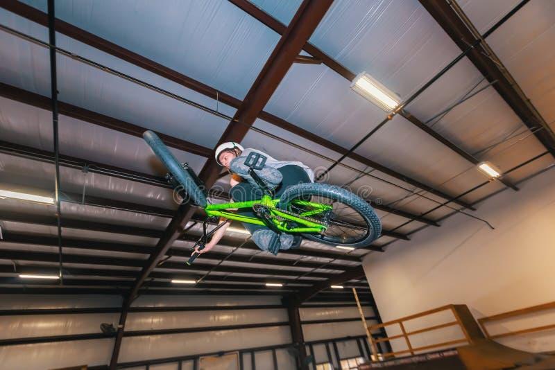 El montar a caballo del hombre en una bicicleta de BMX en los deportes extremos parquea imagenes de archivo