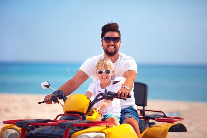 El montar a caballo feliz de la familia, del padre y del hijo en atv quad la bici en la playa arenosa foto de archivo