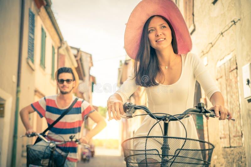 El montar a caballo feliz de los pares monta en bicicleta al aire libre imágenes de archivo libres de regalías