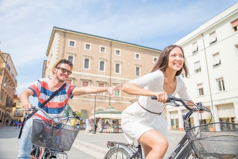 El montar a caballo feliz de los pares monta en bicicleta al aire libre imagenes de archivo