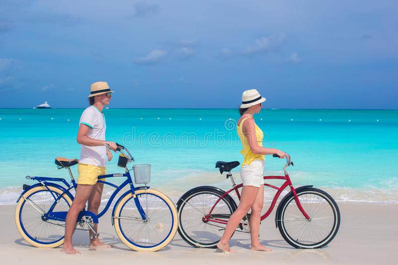 El montar a caballo feliz joven de los pares bikes en la playa arenosa blanca imagen de archivo