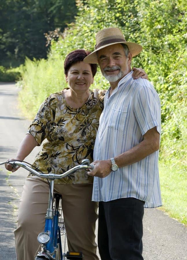 El montar en bicicleta mayor de los pares fotografía de archivo libre de regalías