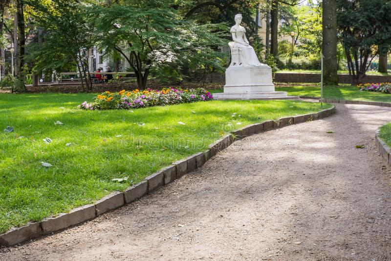 El monumento a Sissi es ocultado por el verdor a lo largo de la 'promenade' de Merano Meran, al lado del puente de los posts El T fotografía de archivo