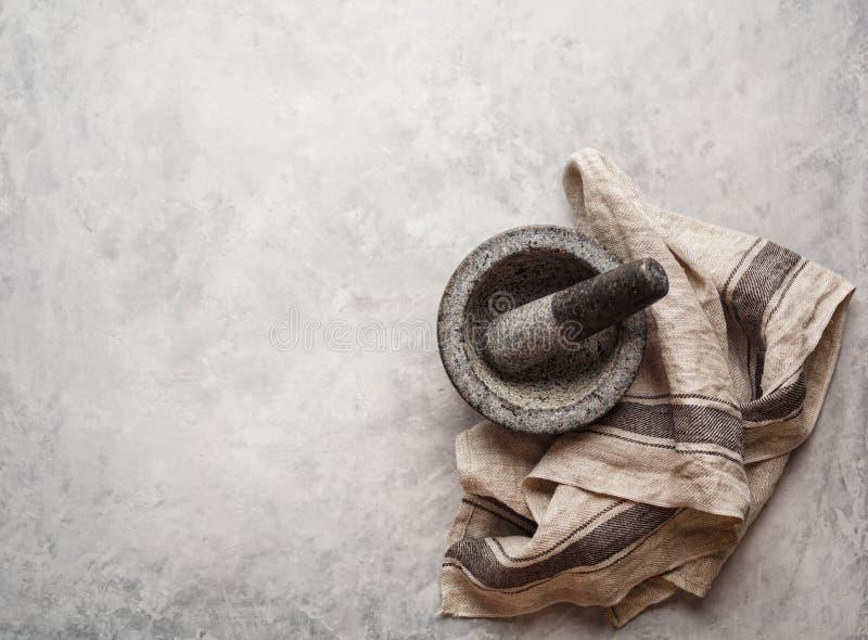 El mortero del granito y la toalla de cocina vacíos en un gris texturizaron el fondo imagen de archivo