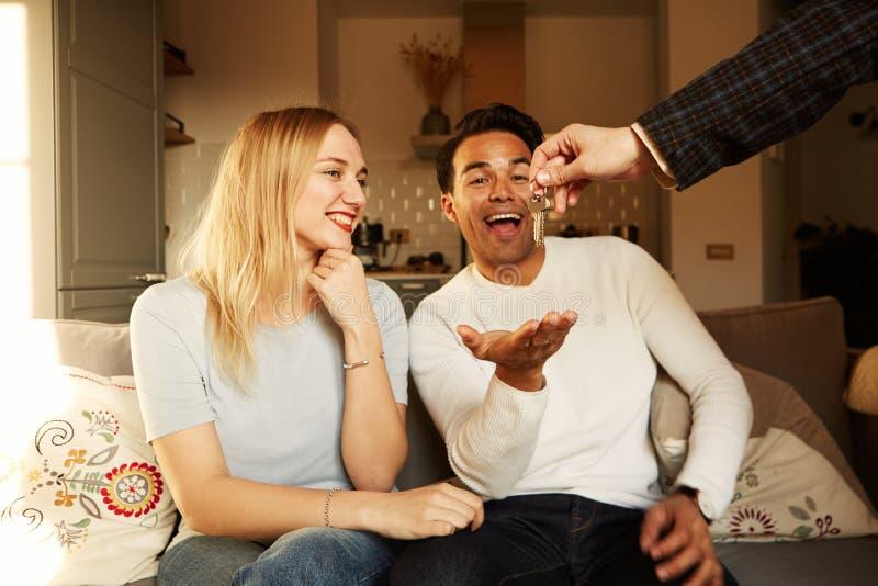 El mostrar joven sonriente feliz de los pares llaves de su nueva casa fotos de archivo