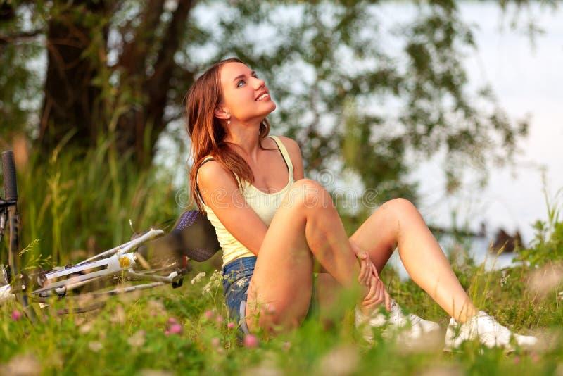 El motorista de la muchacha se sienta en una hierba verde en un bosque o un parque imagenes de archivo