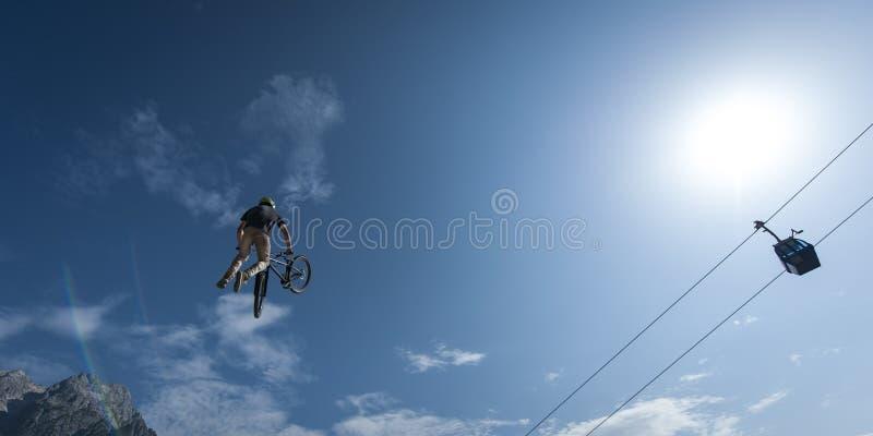 El motorista de la suciedad hace truco con la montaña y el ferrocarril aéreo foto de archivo