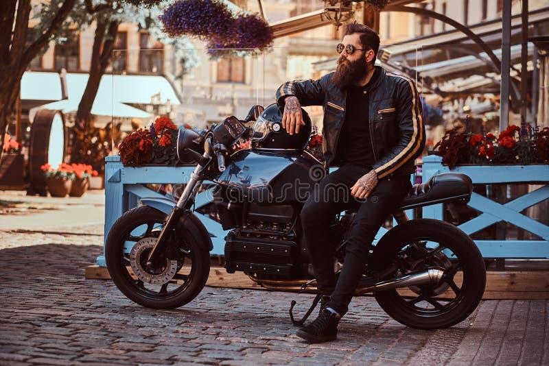 El motorista de moda elegante en gafas de sol se vistió en una chaqueta de cuero negra, sentándose en su motocicleta retra por en fotografía de archivo libre de regalías