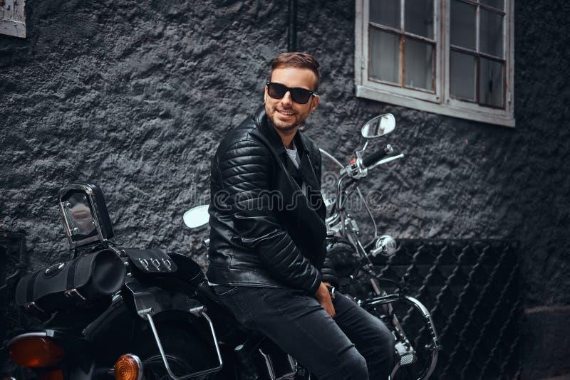El motorista de moda se vistió en una chaqueta de cuero negra y los vaqueros que se sentaban en su motocicleta retra en una calle imagen de archivo libre de regalías
