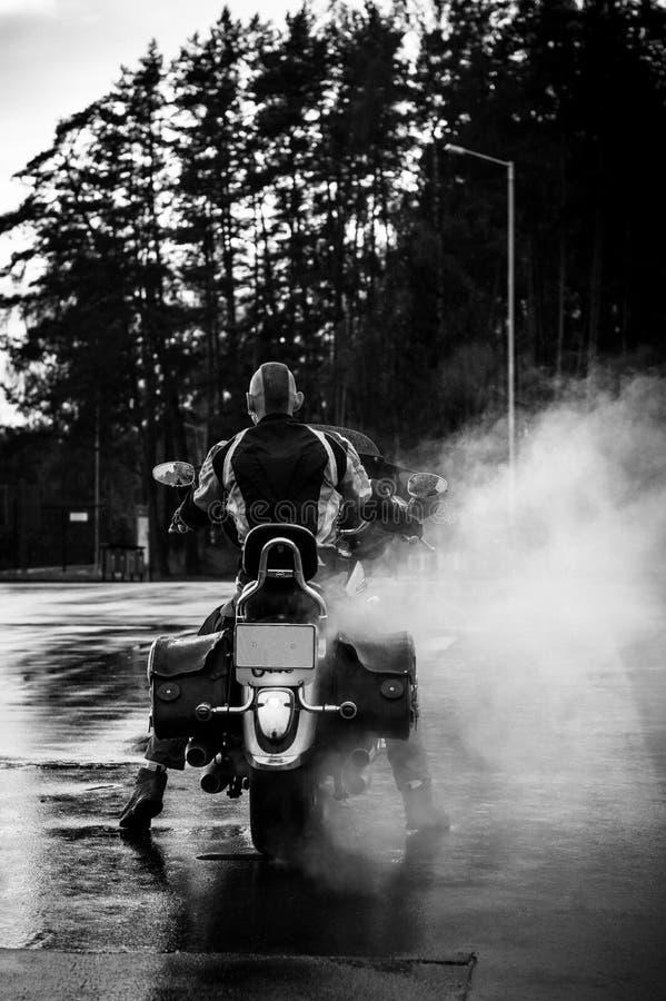 El motorista en su motocicleta está detrás en humo fotos de archivo