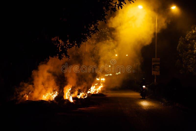 El motorista entra para arriba en humo en la noche quemando la basura imagenes de archivo