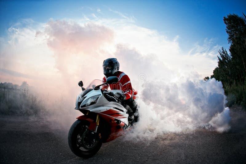 El motorista que permanece en el camino de la bici con el humo del neumático, quema en la demostración del moto La puesta del sol foto de archivo libre de regalías