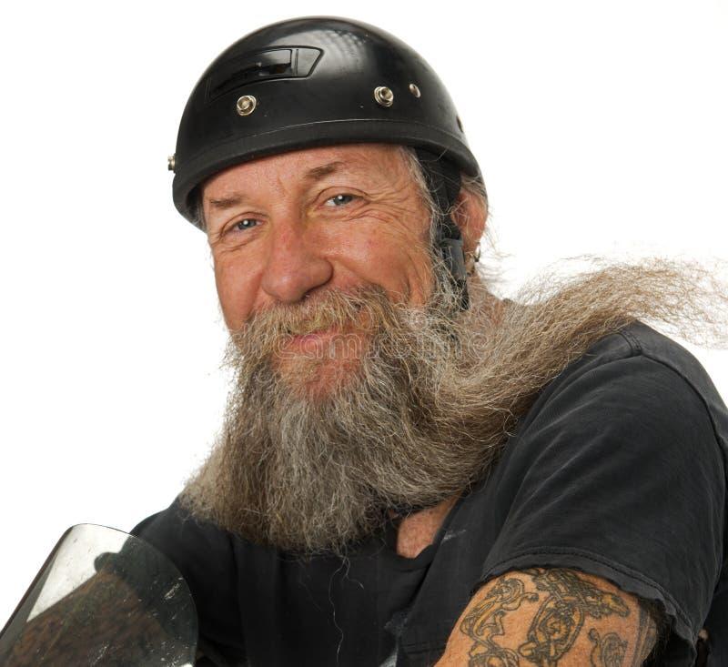 El Motorista Sonríe Mientras Que El Viento Sopla A Través De Su Barba Imágenes de archivo libres de regalías