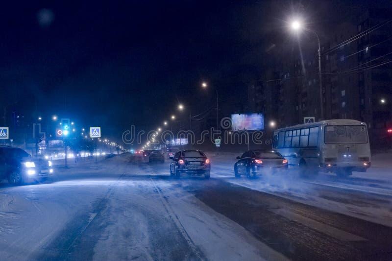 El movimiento de coches el noche del camino del invierno imagen de archivo