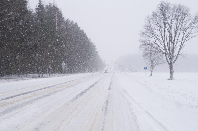 El movimiento por el camino en nevadas fuertes en el invierno imagen de archivo libre de regalías