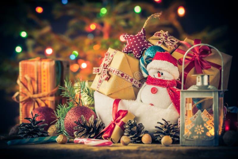 El muñeco de nieve de la tarjeta de Navidad adorna el fondo de las luces del árbol de los regalos imágenes de archivo libres de regalías