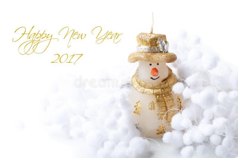 El muñeco de nieve de la vela y la bola de la nieve adornan por Feliz Año Nuevo de la Feliz Navidad en el fondo blanco con el tex imágenes de archivo libres de regalías