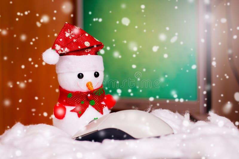 El muñeco de nieve del juguete delante de un ratón del ordenador en el fondo del ordenador, allí es nieve Saludos con Feliz Navid imagen de archivo