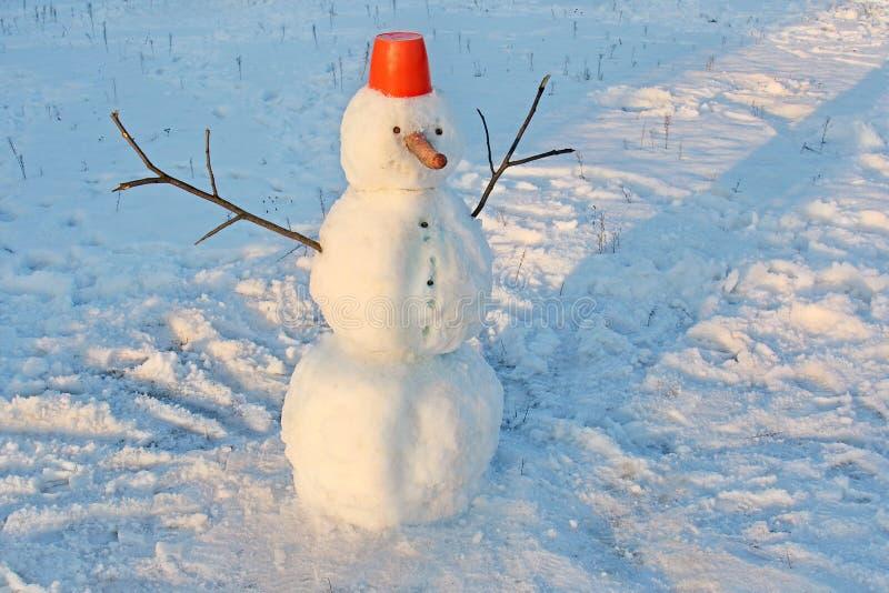 El muñeco de nieve divertido con una nariz de la zanahoria, con un cubo rojo en su cabeza y las palillo-manos en un invierno parq fotografía de archivo libre de regalías