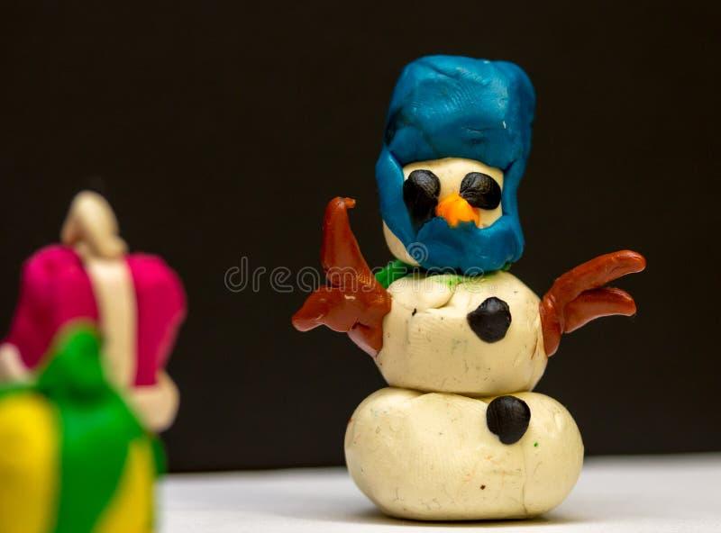 El muñeco de nieve de la plastilina el noche de la Navidad da a todo el mundo los regalos y h imagenes de archivo