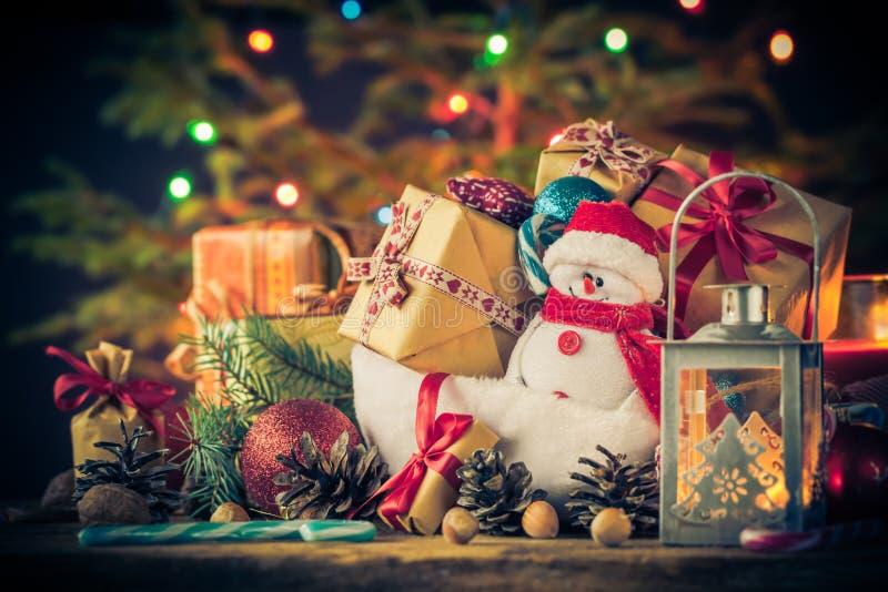 El muñeco de nieve de la tarjeta de Navidad adorna el fondo de las luces del árbol de los regalos imagen de archivo libre de regalías
