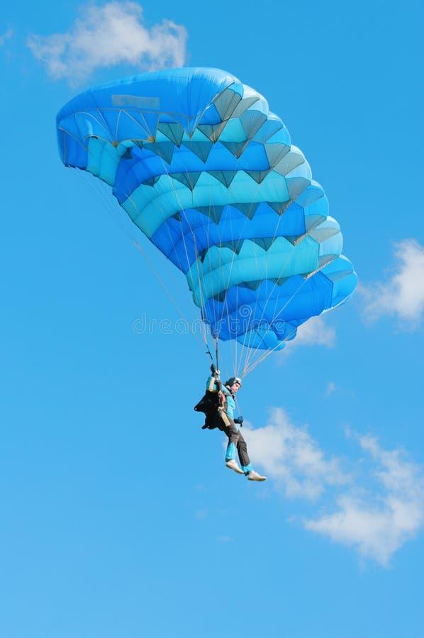 El muchacha-paracaidista bajo un paracaídas azul foto de archivo