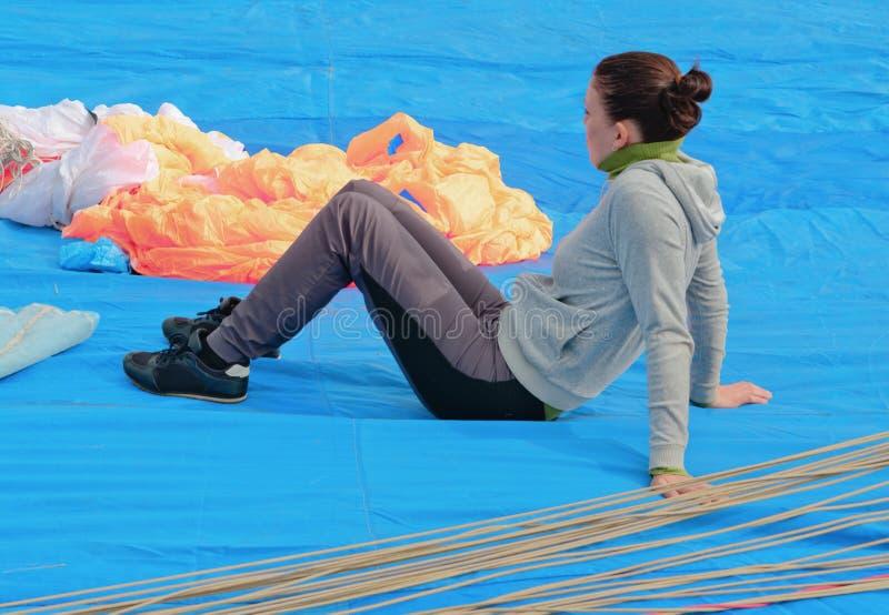 El muchacha-paracaidista joven se sienta en una tela azul imágenes de archivo libres de regalías