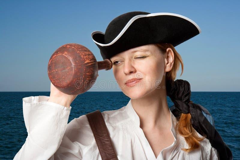 El muchacha-pirata mira en un jarro contra el mar imagenes de archivo