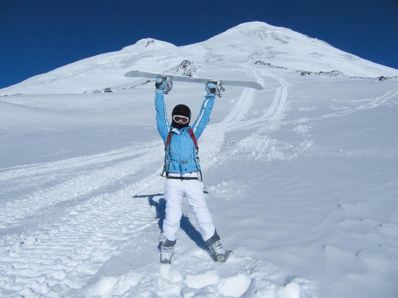 El muchacha-snowboarder se coloca delante de los tops de la montaña que sostienen una snowboard sobre su cabeza en un día soleado foto de archivo libre de regalías