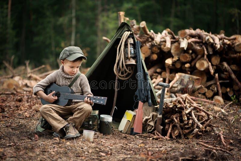 El muchacho, 5 años, parece un trampero, vagabundo, leñador foto de archivo