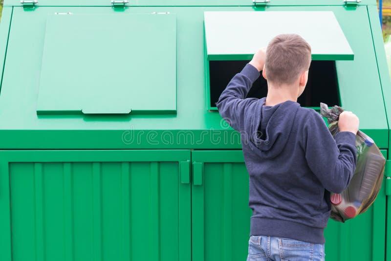 El muchacho abre el tanque inútil para lanzar hacia fuera un bolso negro grande de la basura imagenes de archivo