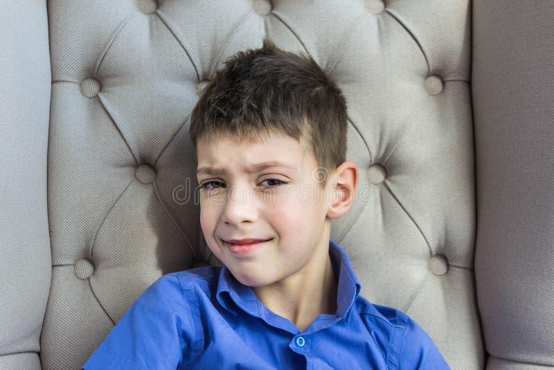 El muchacho adolescente contrariedad que se sienta en casa foto de archivo