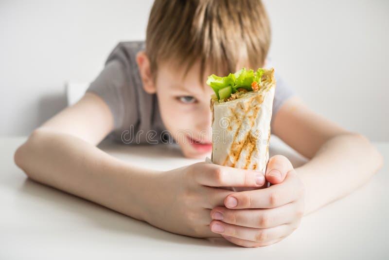 El muchacho adolescente mira shawarma de la comida basura Foco selectivo en shawarma fotos de archivo