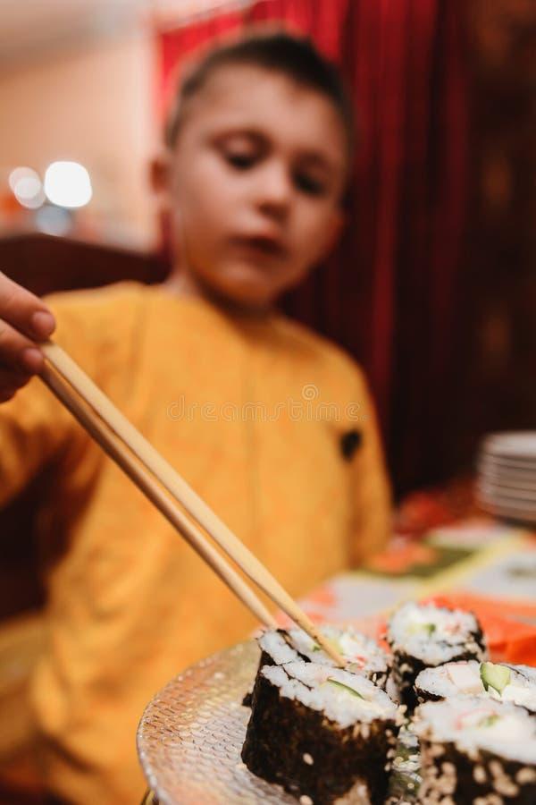 El muchacho adolescente toma el rollo de sushi de la placa para comer fotos de archivo